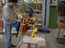 Manipulación de cajas giratorias con un manipulador inteligente INDEVA, que garantiza la ergonomía y la seguridad en el puesto de trabajo.