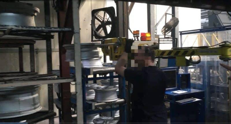 Un manipolatore INDEVA agisce come un'estensione del braccio umano per stoccare i cerchioni dei pneumatici in profondità sugli scaffali.